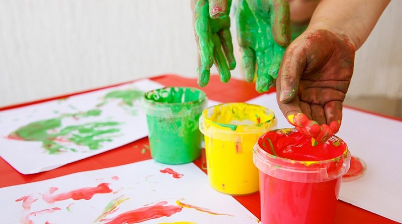 Children dipping fingers in washable, non-toxic finger paints.