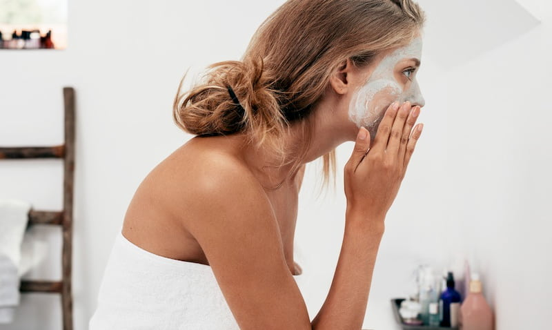 woman applying clay mask on her face
