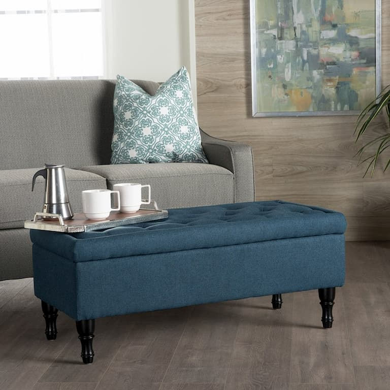 blue ottoman from living room as a coffee table in fornt of the gray sofa bed