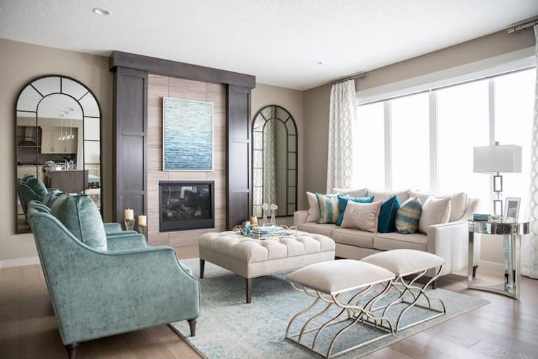 modern living room with beige furnoture pieces and ottoman as a coffee table decorative pillows with design and turquoise armchair
