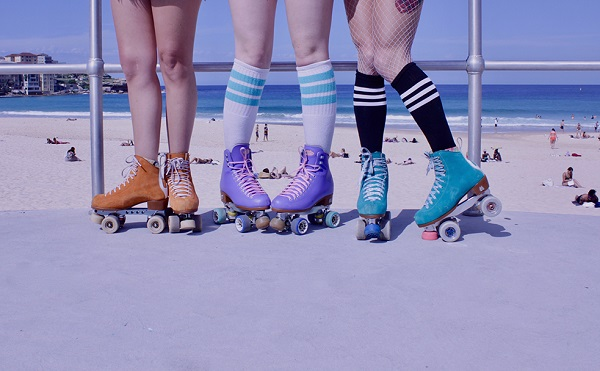picture of girls in different roller skates near the beach