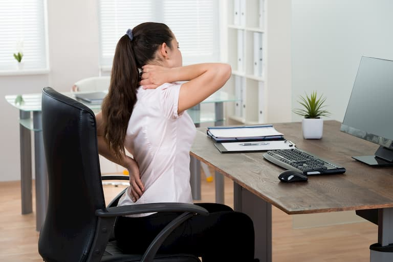 girl sitting on a desk with back pain