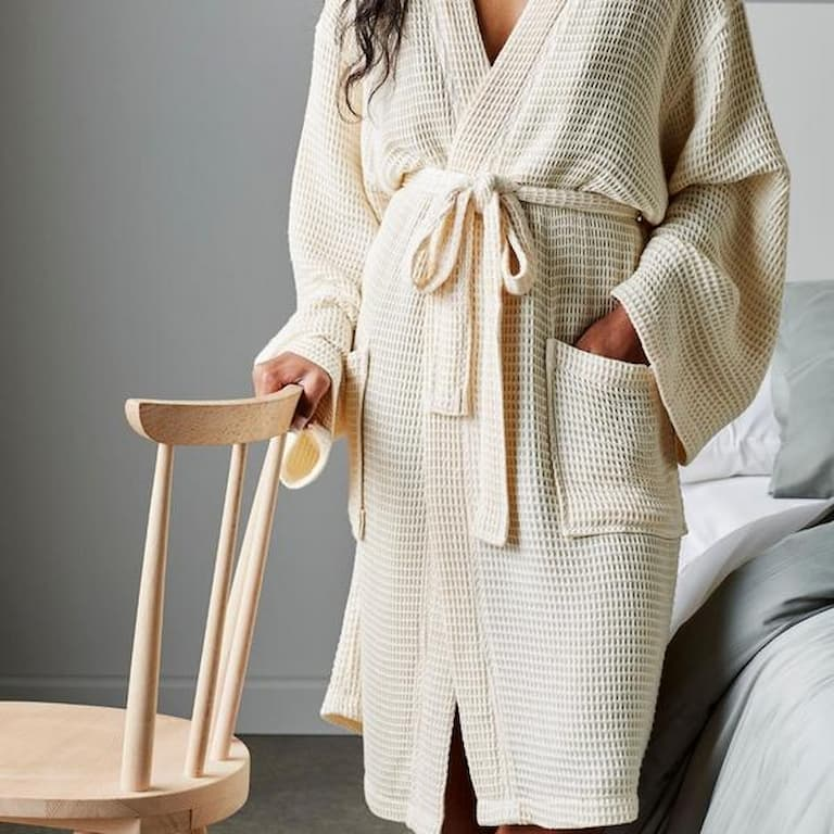 girl standing next to a chair wearing a peach color bathrobe