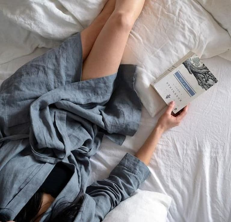 Girl laying in bed reading a book and wearing a blue bathrobe