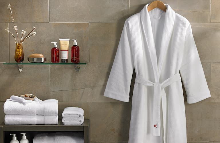 white bathrobe with collar hanging in a bathroom