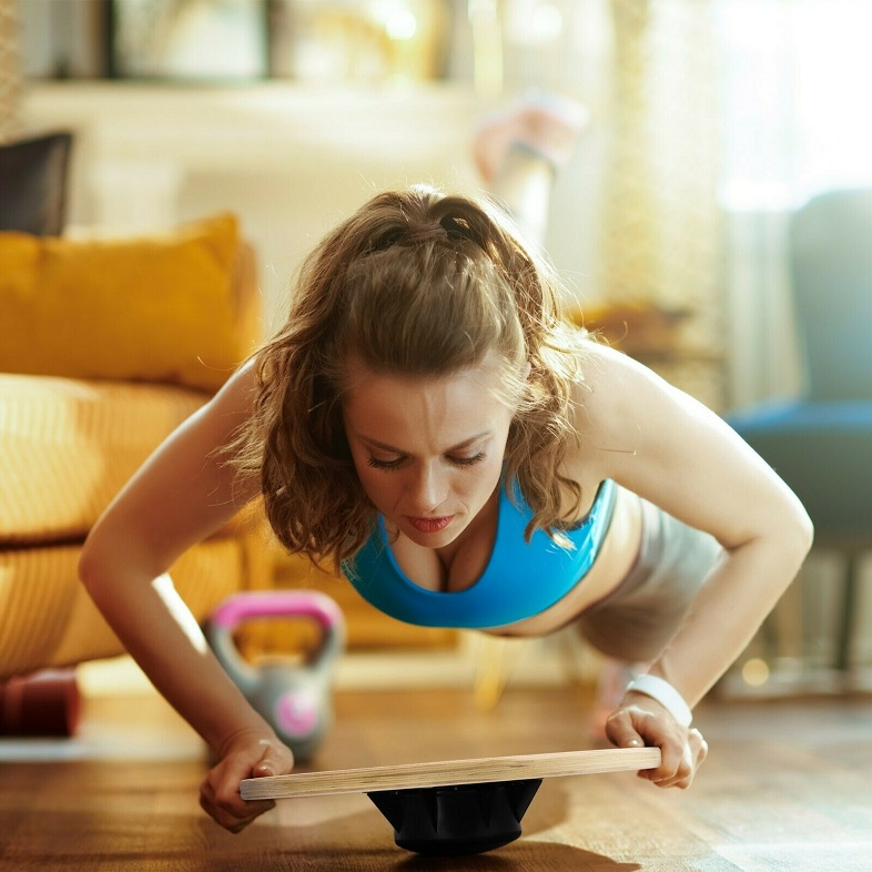 picture of a woman working out at home with a balance board