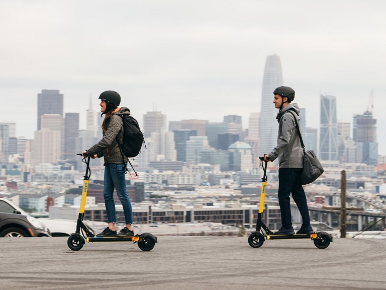 two people riding scooters on the street