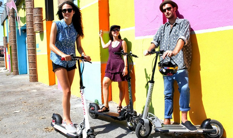 three people standing on scooters with awesome colourful background
