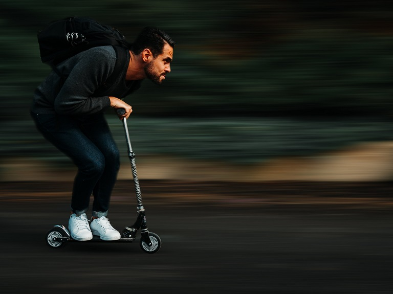a boy driving kick scooter very fast
